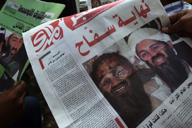 <p>Iraqi men read newspapers displaying front page pictures and headlines that read in Arabic