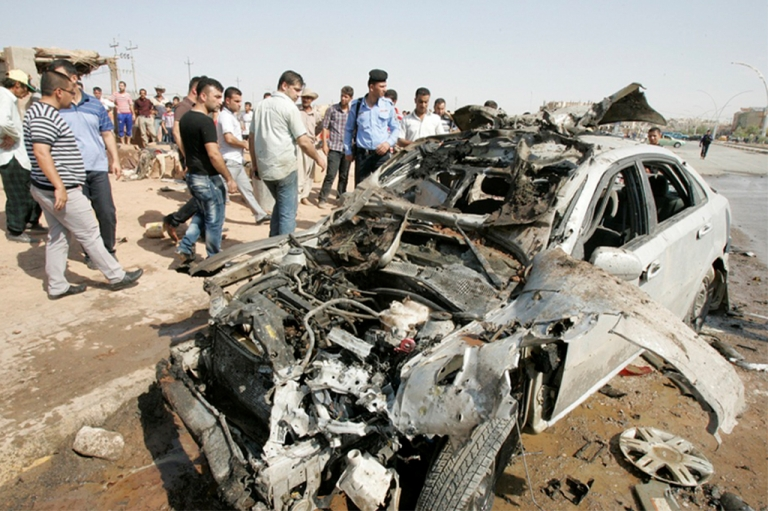<p>Iraqi police and pedestrians look at the shell of a car, one of a series of car bombs targeting army and police patrols in Kirkuk and the eponymous province's towns of Tuz Khurmatu and Dibis which killed at least five people and wounded 20 others on July 23, 2012.</p>