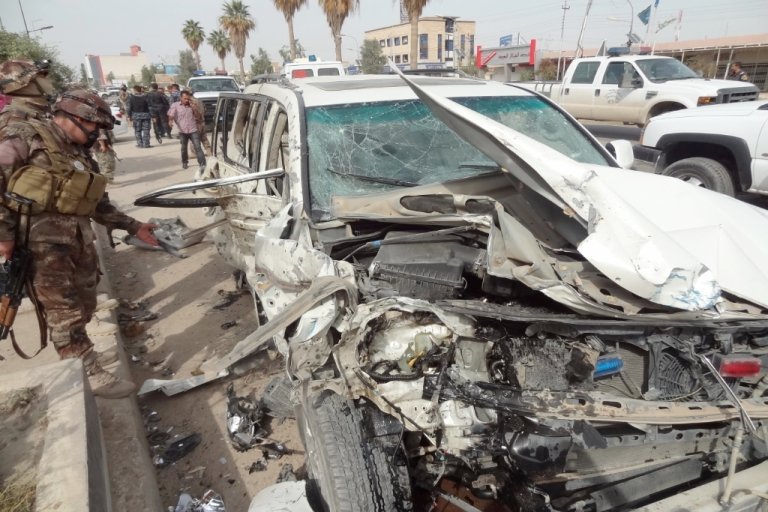 <p>Iraqi security forces inspect the scene of a car bomb explosion outside Kirkuk University on April 15, 2012.</p>