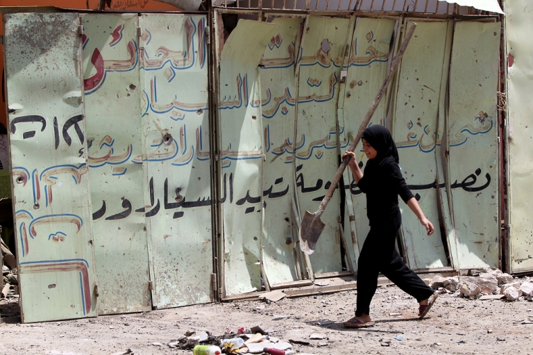 <p>An Iraqi girl walks past the site of a roadside bomb in Baghdad's Karrada district on June 13, 2012 as a wave of bombings and shootings rocked Iraq during a major Shiite religious commemoration, killing scores of people and wounding dozens more.</p>