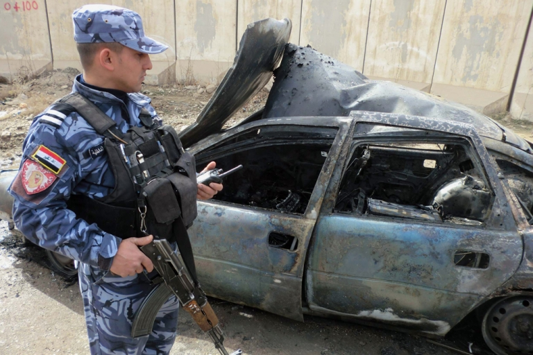 <p>An Iraqi soldier stands close to a destroyed vehicle following a road side bomb on February 13, 2012. A car bomb near a police academy killed 20 police recruits in Baghdad on February 19, 2012.</p>