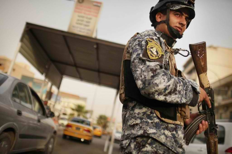 <p>An Iraqi police officer watches cars at a checkpoint on July 20, 2011 in Baghdad. A new report says security in Iraq is deteriorating.</p>