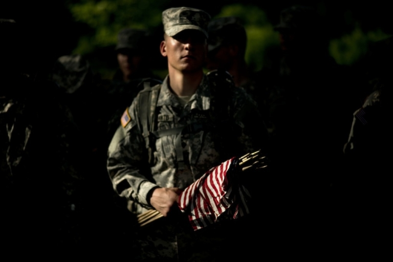 <p>A soldier holds flags at Section 60, an area largely used for those who died while serving in the wars in Afghanistan and Iraq, at Arlington National Cemetery.</p>