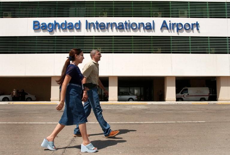 <p>Iraqis walk near Baghdad International Airport in 2004.</p>