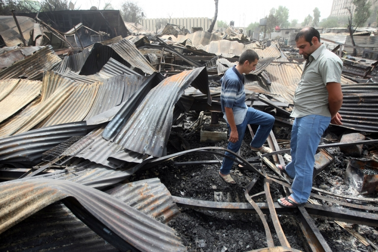 <p>Iraqis look at the damage at the scene of a rocket attack on a residential compound in central Baghdad, on July 5, 2011.</p>