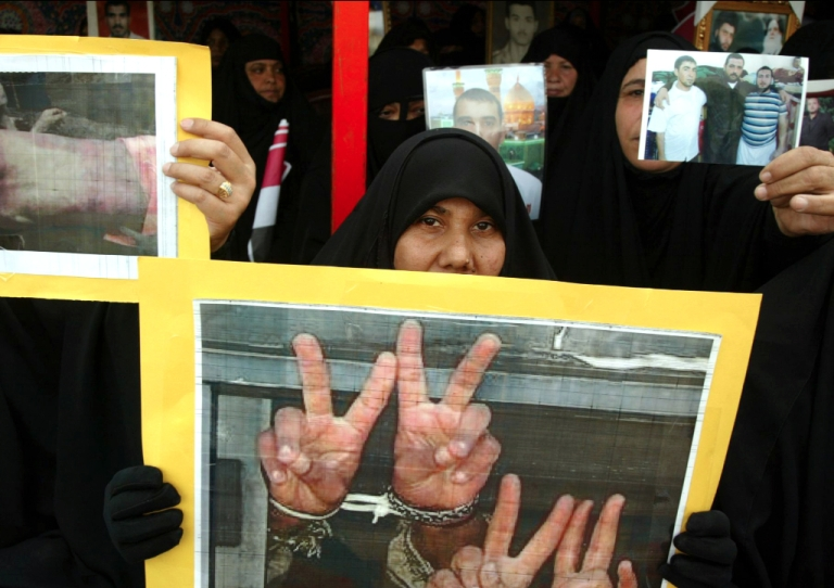 <p>An Iraqi woman hold up a poster during a protest in central Najaf, 150 kms south of Baghdad on November 14, 2009. Some 800 Iraqis from all over the southern provinces gathered in Najaf to call on Iraqi Prime Minister Nuri al-Maliki cancel the death sentences passed on their jailed relatives and to release them.</p>