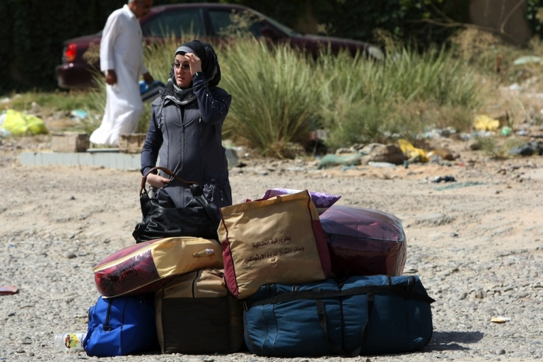 <p>An Iraqi refugee, who had fled to Syria following the 2003 US-led invasion of Iraq, waits next to her belongings upon her arrival in Baghdad on July 3, 2011.</p>