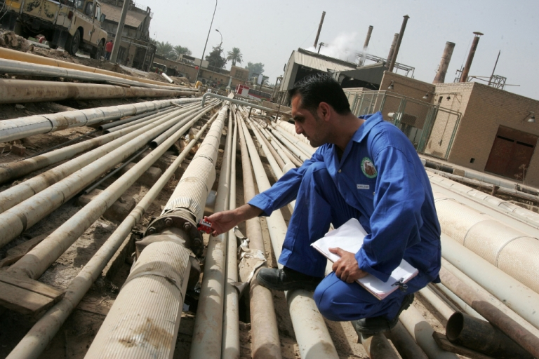 <p>An Iraqi worker examines gas emissions from an oil pipe at a refinery in Baghdad.</p>