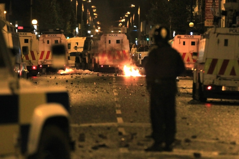<p>A policeman stands burning amid debris and police vehicles in east Belfast, Northern Ireland on June 21, 2011.</p>