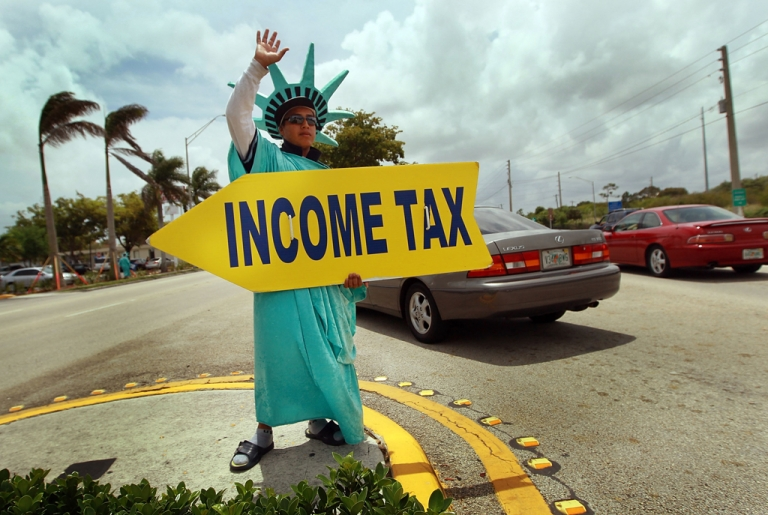 <p>Felipe Castro holds a sign advertising a tax preparation office for people that still need help completing their taxes before the Internal Revenue Service deadline in Miami, Florida. The IRS is offering breaks to taxpayers struggling to file due to unemployment or reduced income.</p>