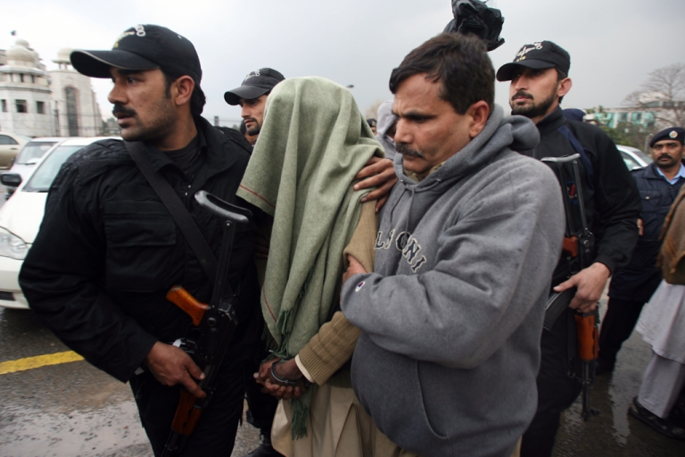 <p>Pakistani policemen escort a man, seen draped in a shawl, after an appearance at the Supreme Court in Islamabad on February 13, 2012. Seven men allegedly held by Pakistan's feared intelligence services on February  appeared in court, an unprecedented development following orders from the country's highest court.   AFP PHOTO/Farooq NAEEM</p>