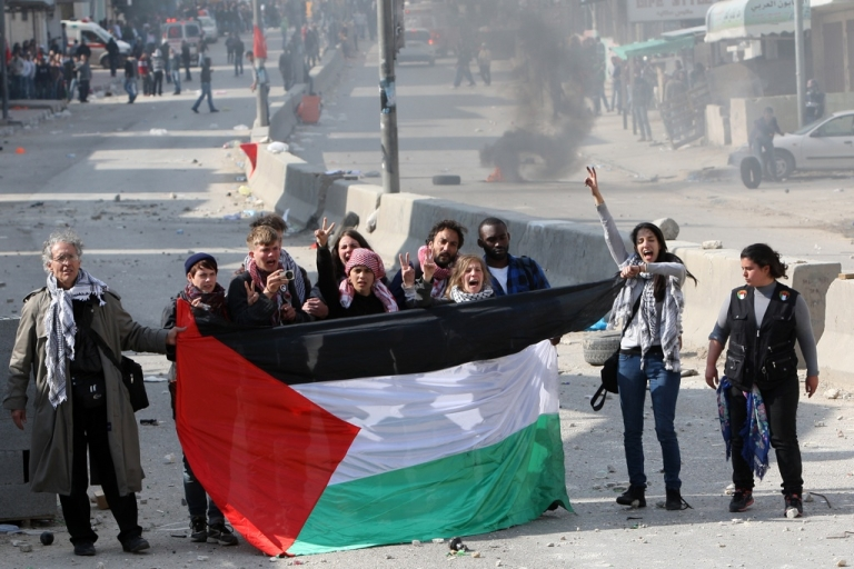 <p>International peace activists hold the Palestinian flag during the commemoration of Land Day in Qalandia, which lies between Jerusalem and the West Bank city of Ramallah on March 30, 2012.</p>