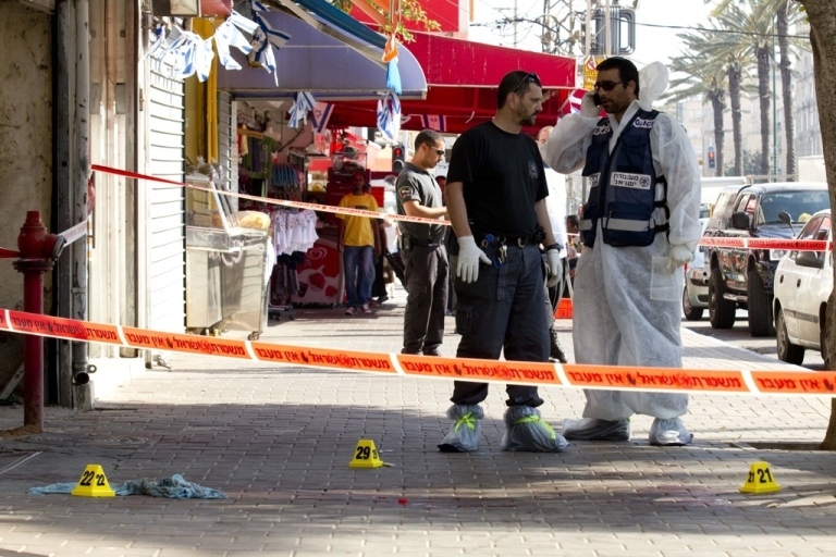 <p>Israeli policemen inspect a crime scene, where a man was stabbed by knife, in the Mediterranean city of Netanya north of Tel Aviv on May 11, 2012.</p>