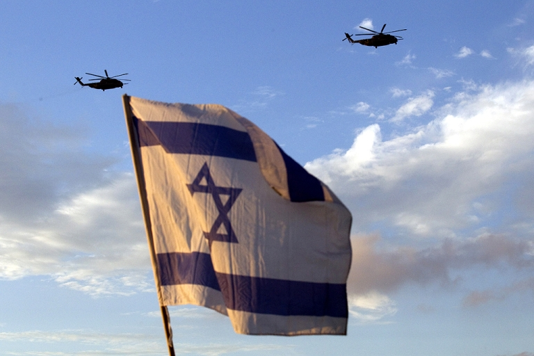 <p>Israelis wave flags as helicopters transporting Israeli soldier Gilad Shalit and his family prepare to land at their home town of Mitzpe Hila following a landmark deal with Hamas which freed Gilad after five years of captivity, on October 18, 2011.</p>