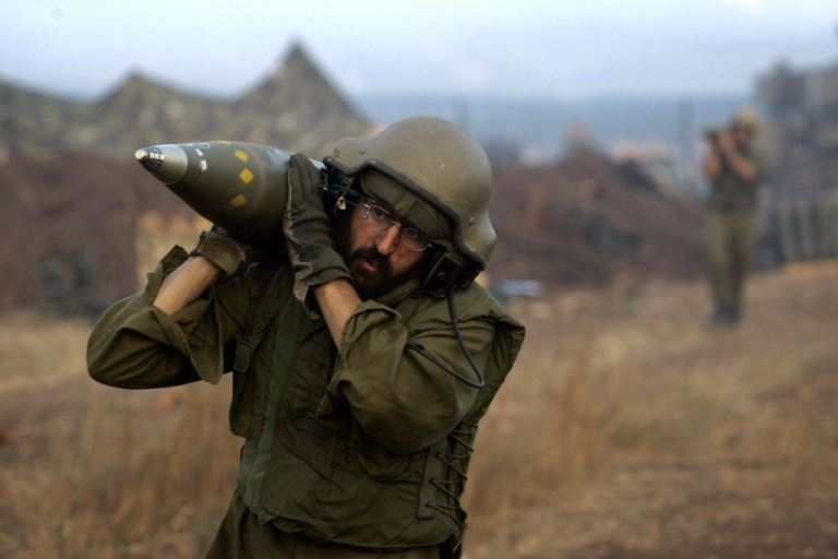 <p>An Israeli soldier carries shells on the border with Lebanon in 2006. Israel is on high alert as the Syrian conflict continues to spill over its borders.</p>