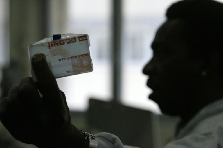 <p>A man shows his Israeli ID card.</p>