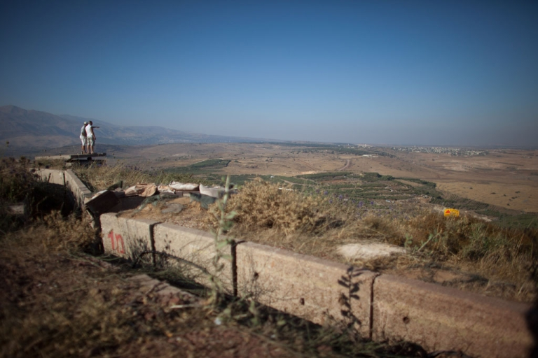 <p>Israelis look at the nearby Syrian village of Jebata al-Khashabn from an Israeli army post near the village of Buqaata at the Israeli side of the border on July 24, 2012 in the Golan Heights.</p>