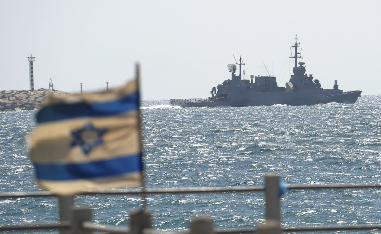 <p>An Israeli flag flutters as a military vessel leaves the navy port of Ashdod in southern Israel on June 5, 2010</p>