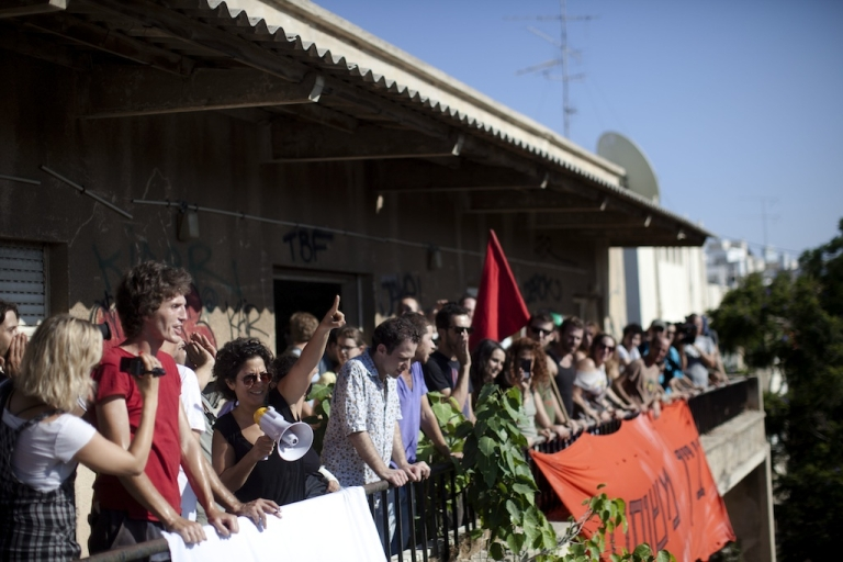 <p>Israelis gather on balcony as they occupy an abandoned public building and protest against the rising cost of living on August 22, 2011 in Tel Aviv, Israel. Demonstrators continue to rally against the government's economic and social policies, which they argue have widened social and financial distance between the state's working poor and rich.</p>