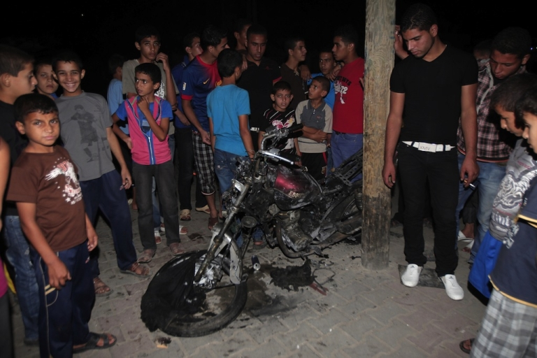 <p>Palestinians gather around the wreckage of a motorcycle targeted by an Israeli aircraft in the town of Rafah in southern Gaza Strip on Oct. 7, 2012. One Palestinian was killed and nine others wounded, Palestinian medical sources told AFP.</p>