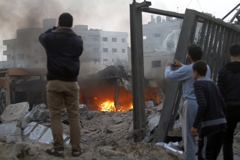 <p>Palestinians take photographs of destruction after Israeli air strikes in Gaza City on November 19, 2012. Israeli air strikes on Sunday killed 31 Palestinians in the bloodiest day so far of its air campaign on the Gaza Strip, as diplomatic efforts to broker a truce intensified.</p>