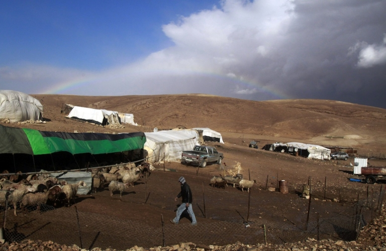 <p>Heavy clouds and a rainbow are seen on the skyline of the the al-Rashaida Bedouin camp in the desert south of the West Bank city of Bethlehem on January 8, 2013.</p>