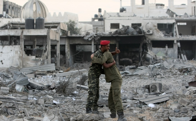 <p>Hamas police officers embrace after their return to their destroyed Al-Saraya headquarters in Gaza City on November 22, 2012, a day after a cease fire was declared between Israel and Hamas. An Egypt-brokered truce took hold in the Gaza Strip after a week of bitter fighting between militant groups and Israel, with both sides claiming victory but remaining wary.</p>