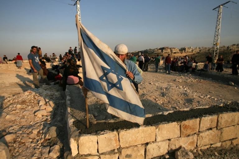 <p>A Jewish settler raises an Israeli flag at the E1 settlement area on December 9, 2007, near the Israeli settlement of Maale Adumim in the West Bank.</p>