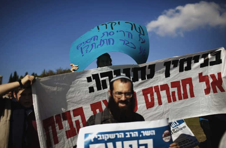 <p>Dozens of Israeli settlers demonstrate in front of the Knesset (Israeli parliament) in Jerusalem on November 7, 2011 against their government's decision to dismantle some of the West Bank settlements. Settlers are protesting and calling for a struggle against the Israeli government's decision to dismantle several settlements by the end of December 2011.</p>