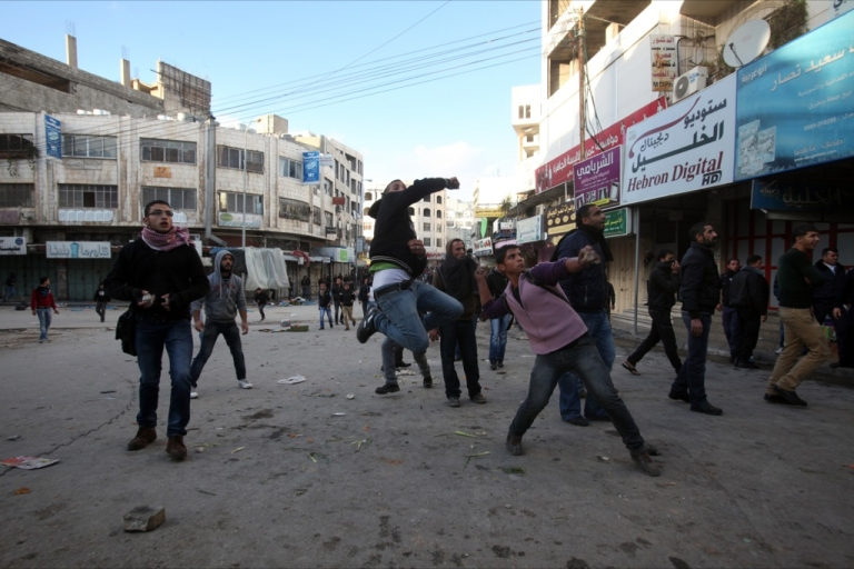 <p>Palestinian youths throw stone at Israeli forces during clashes in the West Bank city of Hebron on December 06,2012.</p>