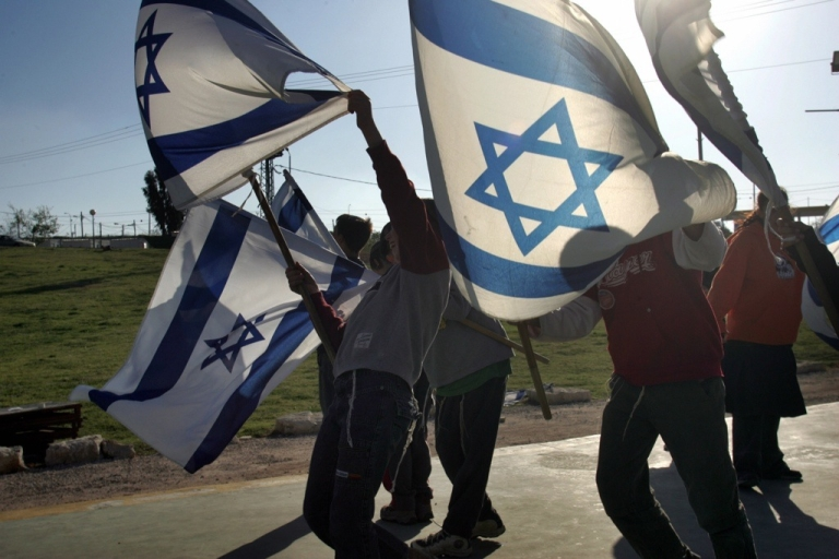 <p>Israeli children wave national flags as they march through the Israeli settlement of Ofra in the West Bank.</p>