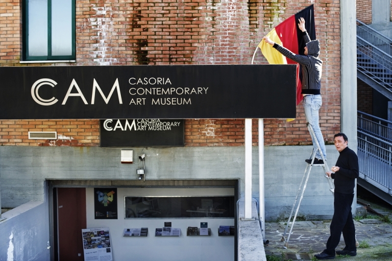 <p>Workers of the CAM Museum (Casoria Contemporary Art Museum) place a German flag at the entrance of the museum in Casoria. Antonio Manfredi, director of the CAM in Naples, planned to burn three works of art a week in protest of budget cuts, he said on April 18, 2012.</p>
