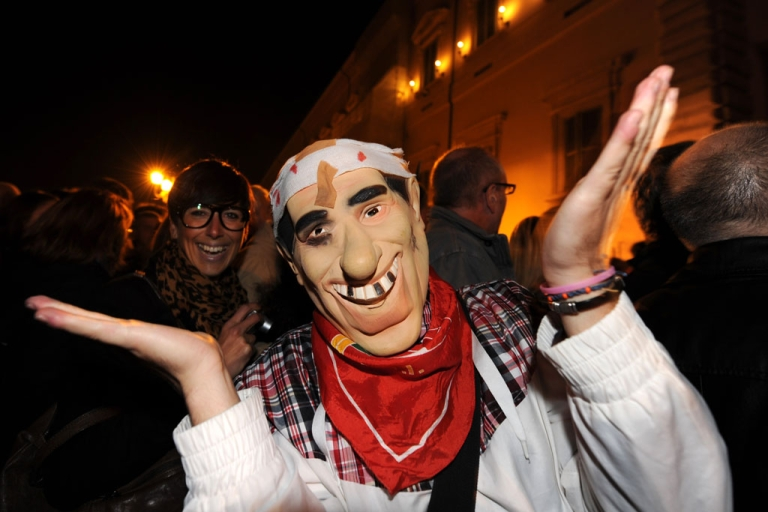 <p>A man wears a Berlusconi mask in front of The Quirinale, the presidential palace in Rome, after Berlusconi resigned on Nov. 12, 2011.</p>