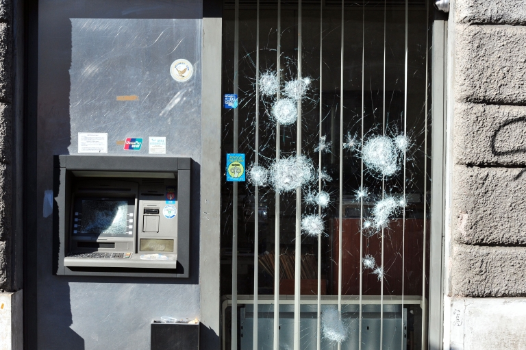<p>A bank with a damaged door and ATM is seen during a demonstration in downtown Rome on October 15, 2011.</p>
