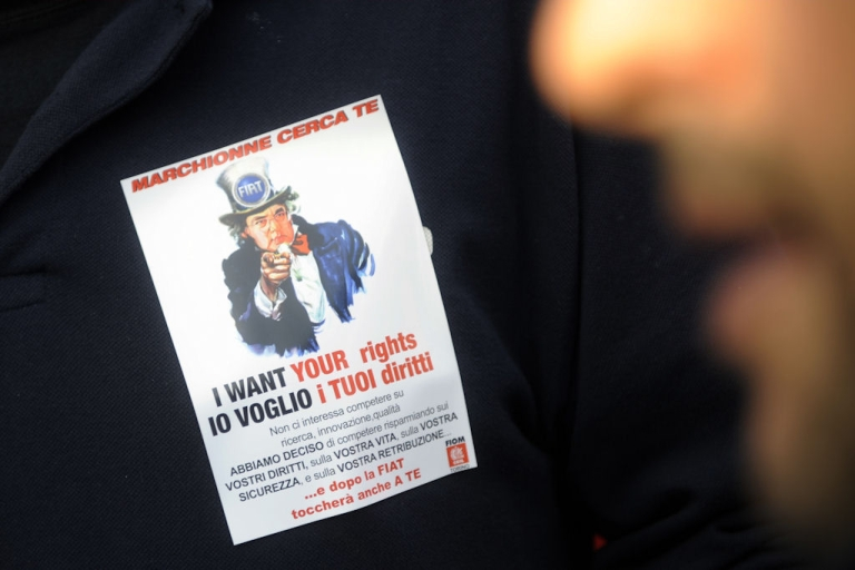 <p>An employee walks by a sticker on Jan. 14, 2011 warning the employees at Turin's Mirafiori plant that Fiat wants to change their contracts as they will be employed under a joint Fiat-Chrysler operating agreement.</p>