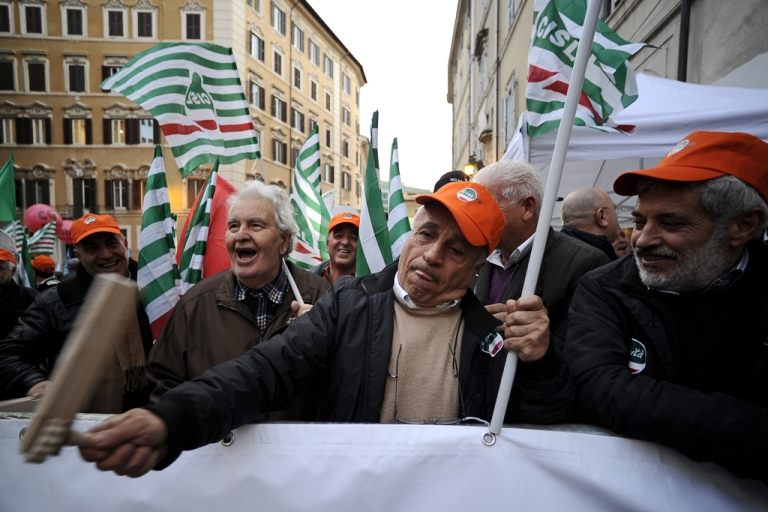 <p>Demonstrators hold flags of trade-unions in front of the Italian parliament during a three-hour strike in protest against a draconian austerity plan of the government on December 12, 2011 in Rome.</p>