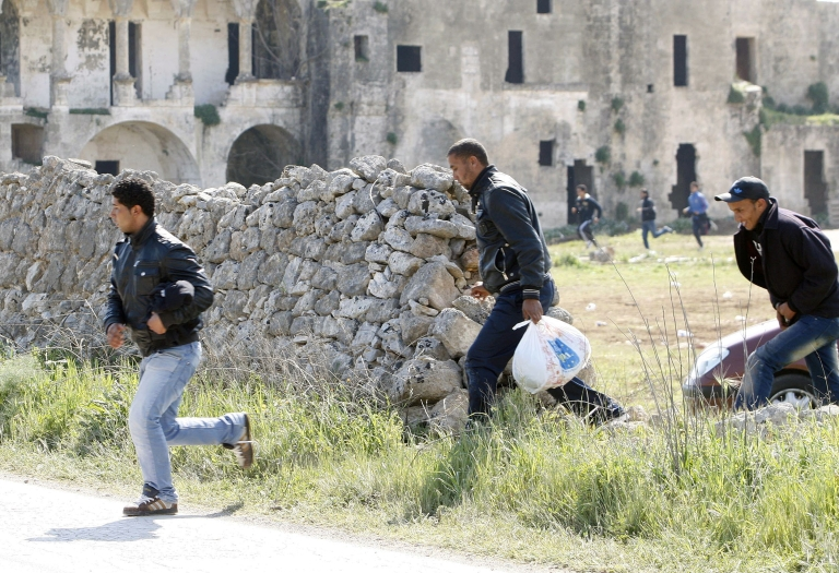<p>Tunisian would-be immigrants who were evacuated from the Italian island of Lampedusa to a reception centre in Manduria in the Puglia region, run after escaping from the camp on April 1, 2011. The Italian government has prepared a plan to accommodate 10,000 migrants on a temporary basis, before repatriating them to Tunisia.</p>