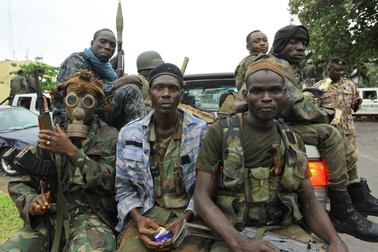 <p>Fighters loyal Alassane Ouattara, one of them wearing a gas mask, prepare for the so-called 'final assault' in front of the Golf Hotel in Abidjan on April 5, 2011.</p>