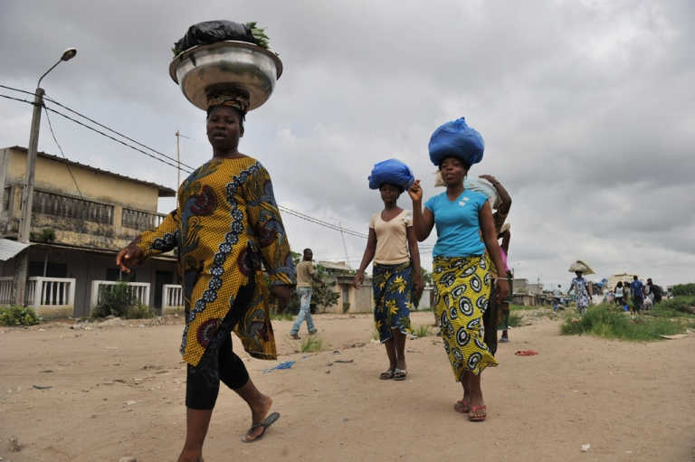 <p>Women carry goods on their heads as they return from shopping at the Abobo market, a suburb of Abidjan, on April 7, 2011 where life started returning to normal after weeks of clashes between forces loyal to internationally recognized President Alassane Ouattara and those backing strongman Laurent Gbagbo.</p>