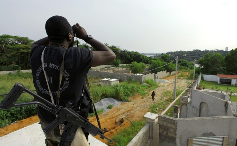<p>A member of Forces loyal to Ivory Coast's internationally recognised president Alassane Ouattara looks through binoculars ahead of an attack on the residence of Laurent Gbagbo in Abidjan on April 6, 2011.</p>