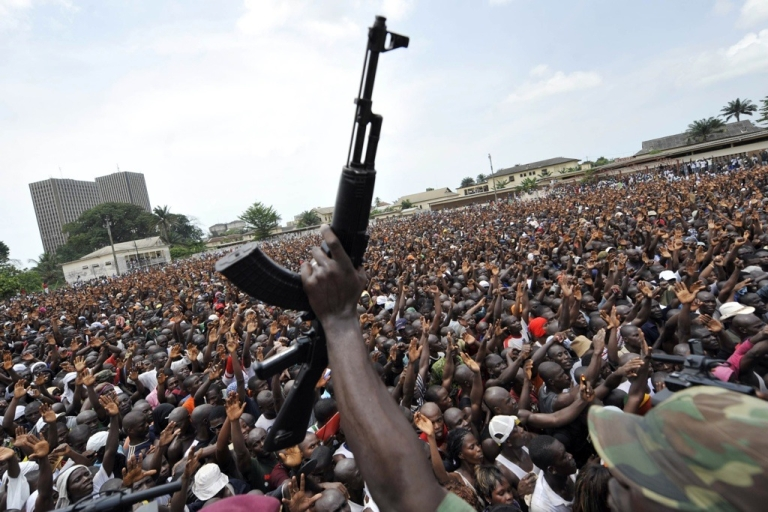 <p>A soldier in the Ivory Coast Army brandishes his gun in front of thousands of young supporters of Ivorian strongman Laurent Gbagbo. The young men gathered to enroll in the Ivorian army, on March 21, 2011 in Abidjan. Fervent backers of Gbagbo streamed to enlist in his armed forces as the United Nations faced pressure to do more to protect civilians in post-election bloodshed in which more than 400 people have been killed. Gbagbo, who refuses to cede power after disputed November polls, is seeking to boost his army and quash efforts by fighters backing internationally recognized president Alassane Ouattara to seize the economic capital Abidjdan.</p>