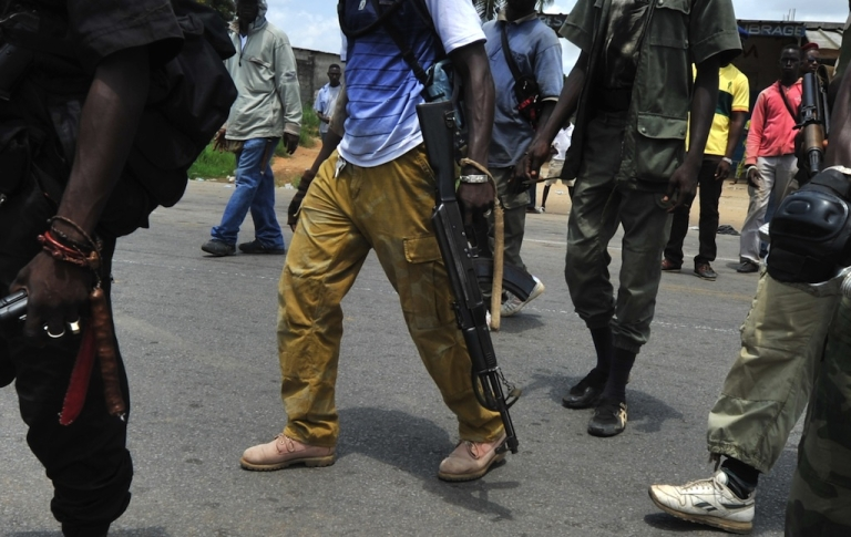 <p>Armed militiaman backing internationally recognized president Alassane Ouattara walk at a makeshift checkpoint on March 24, 2011, in the Abobo district of Abidjan.</p>