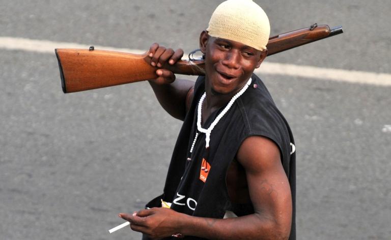 <p>A millitaman loyal to Alassane Ouattara walks along a street in Abidjan on April 1, 2011.</p>