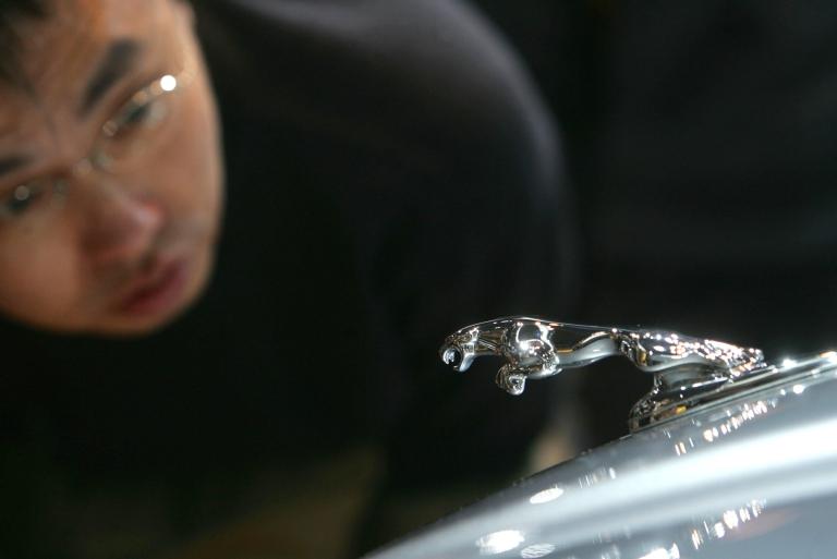 <p>A visitor admires a Jaguar sedan on Nov. 19, 2006 in Beijing, China.</p>