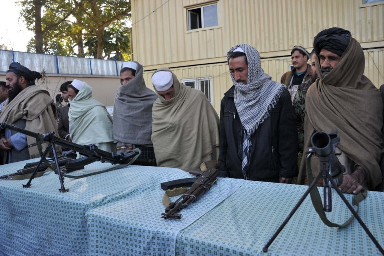 <p>Former Taliban fighters stand next to their weapons as they join a peace and reconciliation process at a ceremony in Jalalabad, Afghanistan, on Jan. 13, 2013. As the capital of Nangarhar province, Jalalabad is one of the most important economic and political centers in the eastern part of the country.</p>