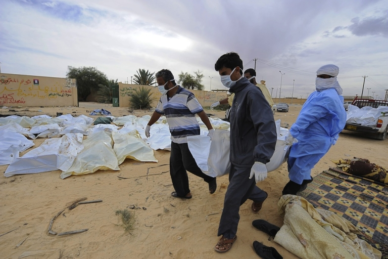 <p>Libyans carry a body bag containing the remains of a loyalist fighter believed to have been killed in a NATO bombing before the capture of Muammar Gaddafi in the Libyan town of Sirte on Oct. 22, 2011.</p>