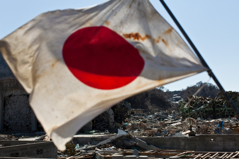 <p>A Japanese flag waves in the wind amid the wreckage and devastation of the March 11 tsunami in the town centre of Onagawa, Miyagi prefecture, on April 6, 2011.</p>