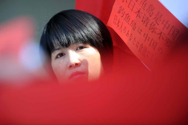 <p>A member of the Chinese minority in Hungary looks on during a demonstration at the Japanese Embassy in Budapest on September 24, 2012 during a protest over uninhabited but disputed islands in the East China Sea, known as Diaoyu in China and Senkaku in Japan, which Tokyo controls but Beijing proclaims as its