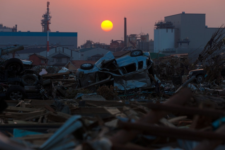 <p>The sun sets on April 13, 2011, over debris still piled up nearly five weeks after the earthquake and tsunami disaster devastated the city of Ishinomaki in Miyagi prefecture.</p>