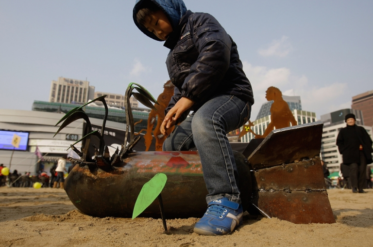 <p>A South Korean boy plays with nuclear bomb is exhibits during a rally held to commemorate the Fukushima nuclear disaster on the eve of the one year anniversary of Japan's earthquake and tsunami on March 10, 2012 in Seoul, South Korea.</p>